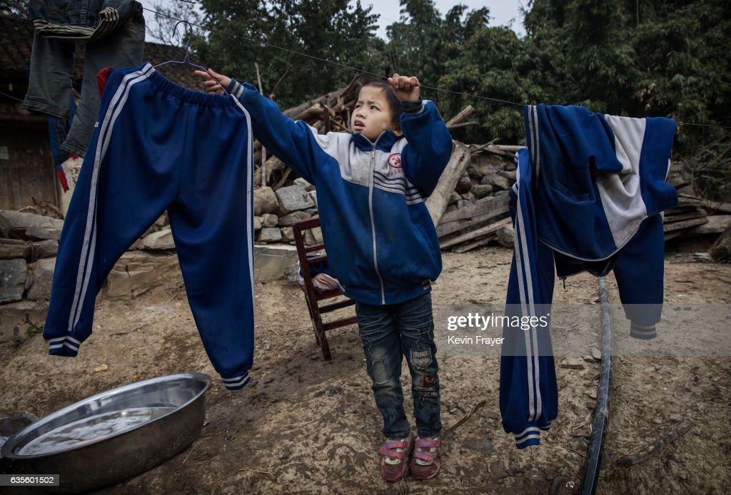 Luo Hongniu, 8, hangs laundry after washing clothes with her siblings. Photo by Kevin Frayer/Getty Images
