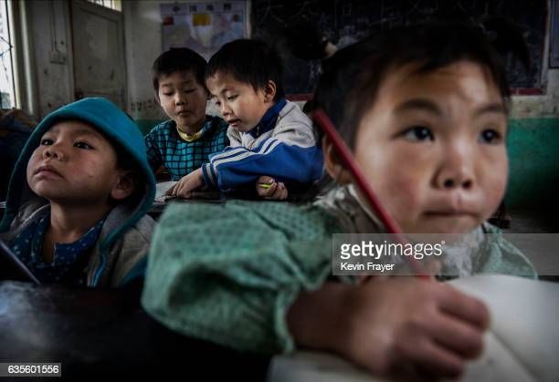 'Left behind' child Luo Lie background right do schoolwork in class at a local school on December 16 2016 in Anshun China Like millions of Chinese...