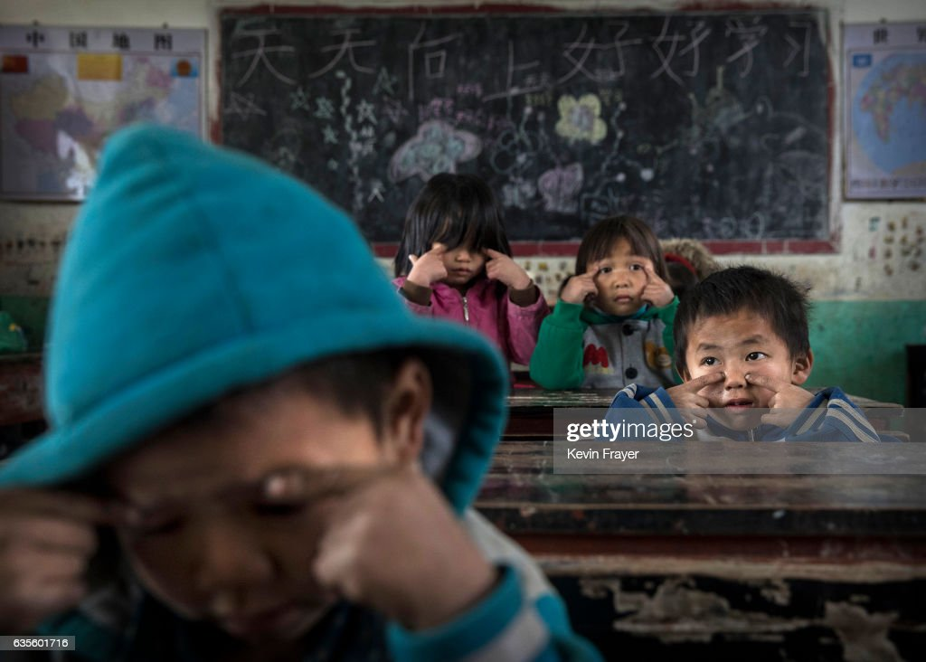 Luo Lie, 5 (R) does eye exercises with classmates at a local school. Local schools, educators and community charities often try to help take care of the children. Still, many children feel the absence of interaction with their mother and/or father, creating a generation of lonely kids who experts worry may be prone to anxiety, poor school performance, and depression. Photo by Kevin Frayer/Getty Images