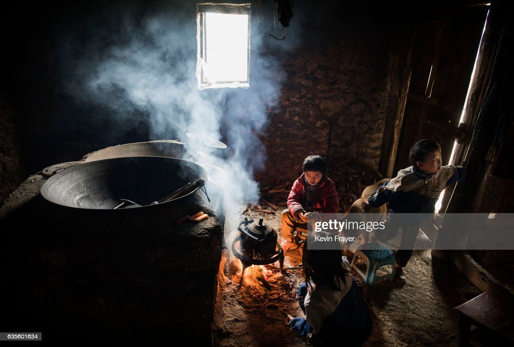 Luo Hongni, 11, Luo Lie, 5, right, and Luo Hongniu, 8, top, sit around a fire at the family home. Photo by Kevin Frayer/Getty Images