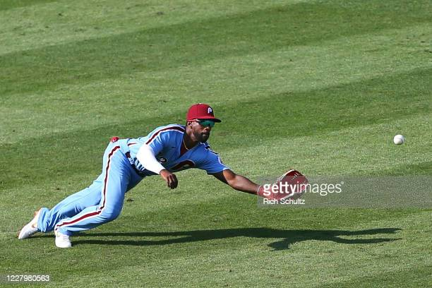 Left fielder Andrew McCutchen of the Philadelphia Phillies dives but can't make a catch on a single hit by Ronald Acuna Jr. #13 of the Atlanta Braves...