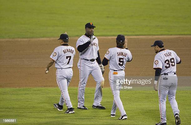 Left fielder Barry Bonds of the San Francisco Giants congratulates teammates Marvin Benard Tsuyoshi Shinjo and Pedro Feliz after defeating the St...
