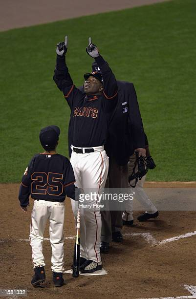 Left fielder Barry Bonds of the San Francisco Giants stands in front of his son Nikolai points skyward as he stands on home plate after hitting his...