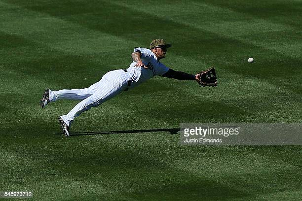 Left fielder Brandon Barnes of the Colorado Rockies makes a diving catch for the first out of the fourth inning against the Philadelphia Phillies at...