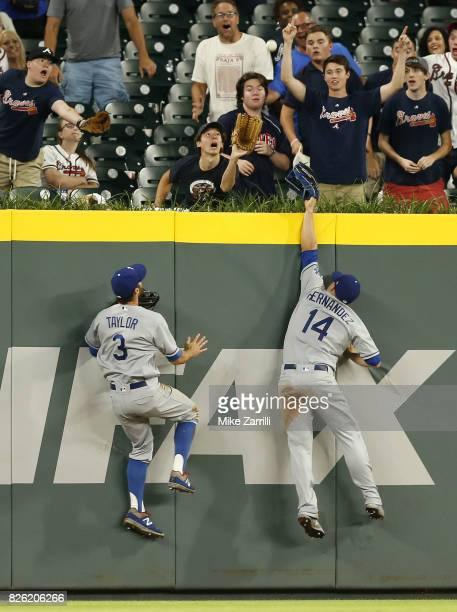 Left fielder Chris Taylor and centerfielder Kike Hernandez jump for a ball hit just out of reach by second baseman Ozzie Albies of the Atlanta Braves...