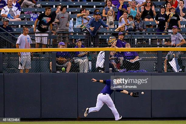 Left fielder Corey Dickerson of the Colorado Rockies comes up short on an RBI ground rule double off the bat of Cameron Maybin of the San Diego...