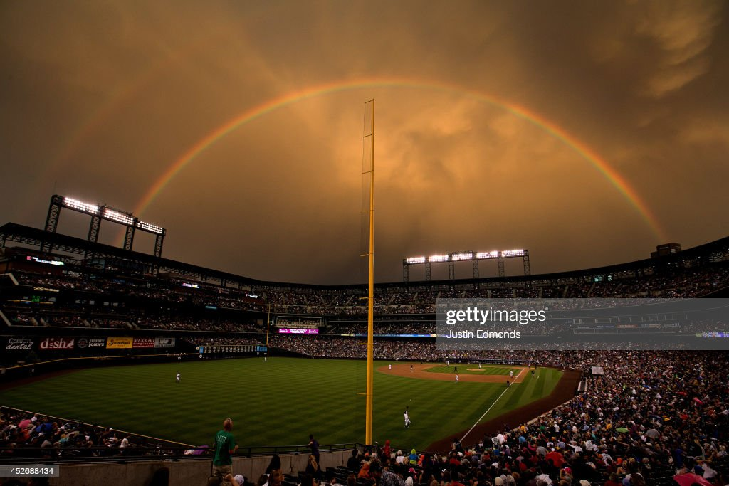 Left fielder Corey Dickerson #6 of the Colorado Rockies makes a catch on a fly ball off the bat of Gaby Sanchez #17 of the Pittsburgh Pirates for the third out of the sixth inning as a double rainbow illuminates the stadium at Coors Field on July 25, 2014 in Denver, Colorado.