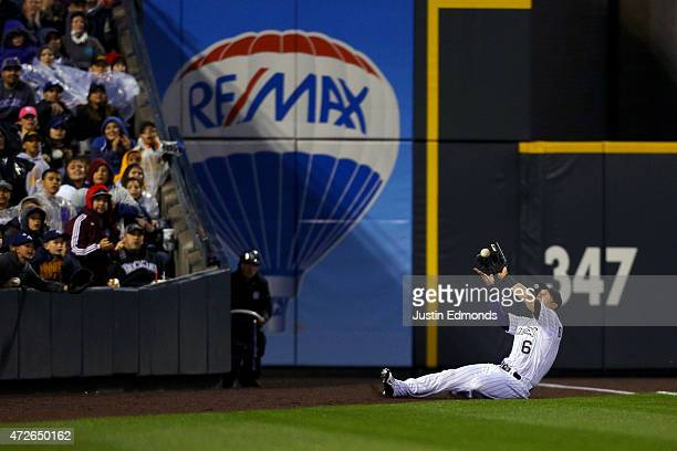 Left fielder Corey Dickerson of the Colorado Rockies makes a sliding catch in foul territory on a ball off the bat of Yasmani Grandal of the Los...