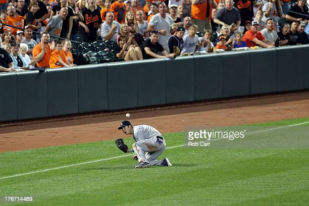 Left fielder Corey Dickerson of the Colorado Rockies misses catching a two RBI single by Nick Markakis of the Baltimore Orioles during the third...
