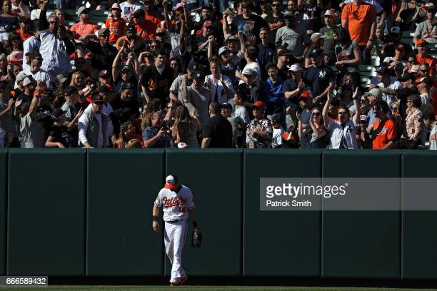 Left fielder Craig Gentry of the Baltimore Orioles walks away from the outfield wall after he could not make a catch on a home run hit by Aaron Judge...