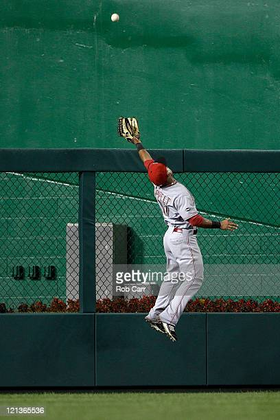 Left fielder Dave Sappelt of the Cincinnati Reds misses a solo home run by Jesus Flores of the Washington Nationals during the fifth inning at...