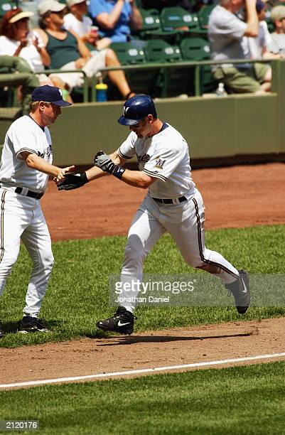 Left fielder Geoff Jenkins of the Milwaukee Brewers celebrates with third base coach Rich Donnelly as he heads home during the interleague game...