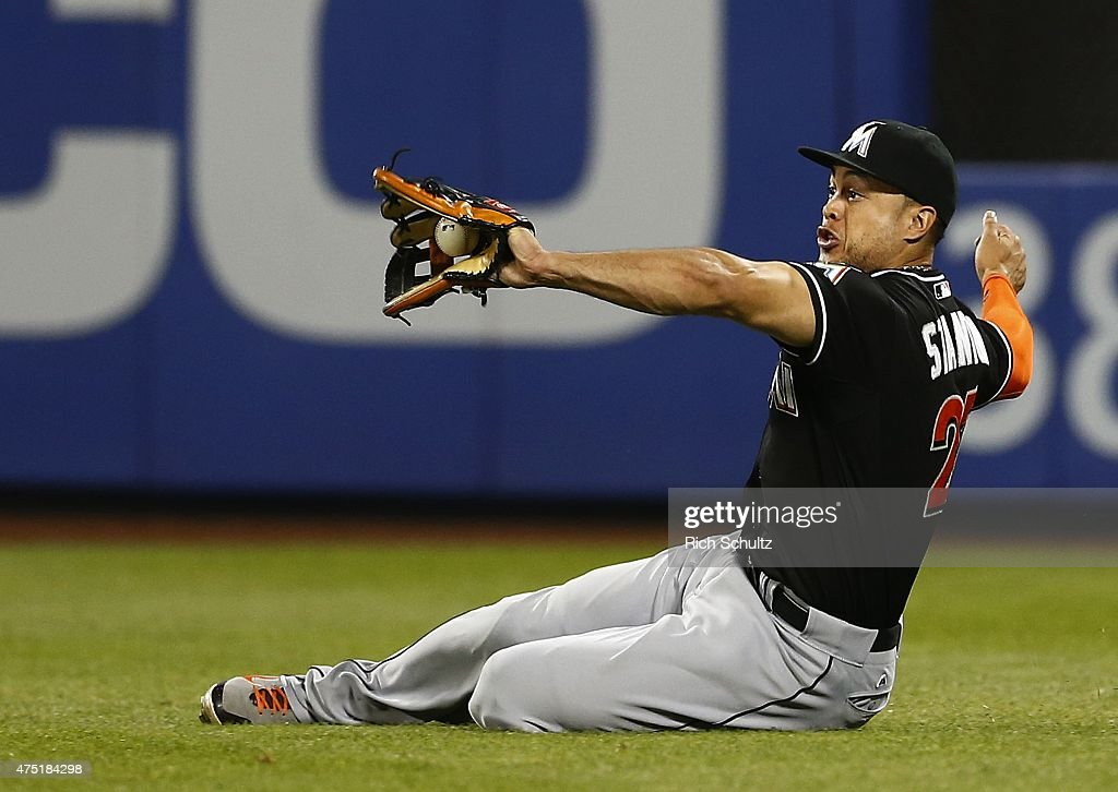 Left fielder Giancarlo Stanton #27 of the Miami Marlins slides to make a catch on a ball hit by Wilmer Flores #4 of the New York Mets during the seventh inning on May 29, 2015 at Citi Field in the Flushing neighborhood of the Queens borough of New York City.
