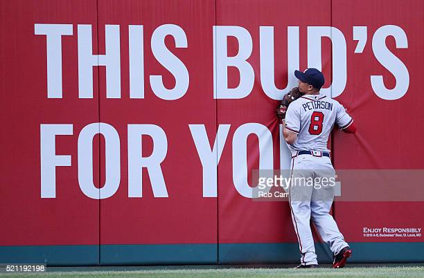 Left fielder Jace Peterson of the Atlanta Braves runs into the wall after catching a ball hit a by Anthony Rendon of the Washington Nationals for the...