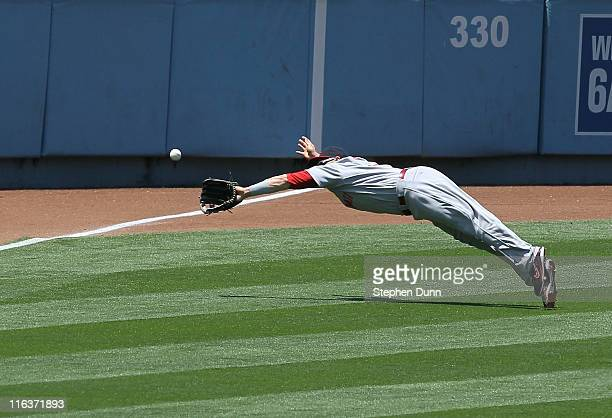 Left fielder Jonny Gomes of the Cincinnati Reds makes a diving catch of a line drive hit by James Loney of the Los Angeles Dodgers to end the third...