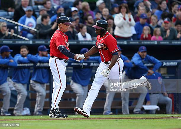 Left fielder Justin Upton of the Atlanta Braves is congratulated by third base coach Brian Snitker after Upton's first inning home run during the...