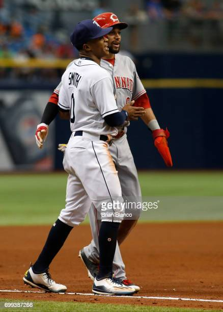 Left fielder Mallex Smith of the Tampa Bay Rays laughs and hugs Billy Hamilton of the Cincinnati Reds after catching Hamilton in the round down at...