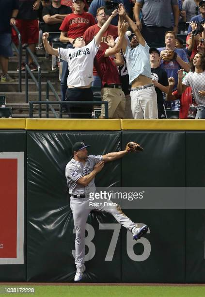 Left fielder Matt Holliday of the Colorado Rockies collides with the wall as fans try to catch the home run by AJ Pollock of the Arizona Diamondbacks...