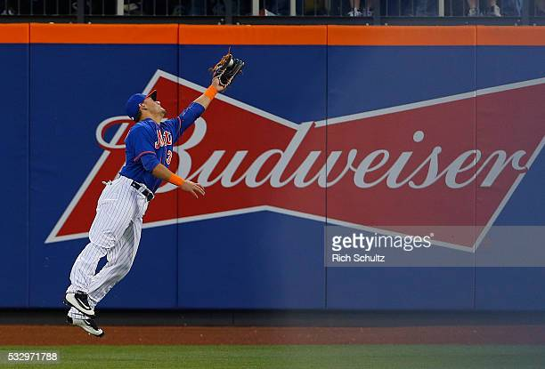 Left fielder Michael Conforto of the New York Mets can't hold onto a ball hit by Anthony Rendon of the Washington Nationals for a two run double...