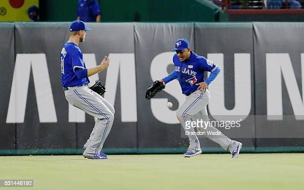 Left fielder Michael Saunders left and center fielder Ezequiel Carrera right of the Toronto Blue Jays are unable to catch a triple hit by Ryan Rua of...