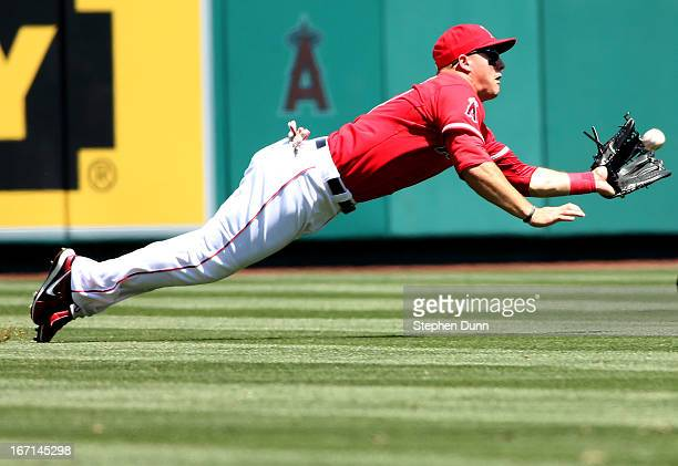 Left fielder Mike Trout of the Los Angeles Angels of Anaheim dives to catch a line drive hit by Brayan Pena of the Detroit Tigers in the second...