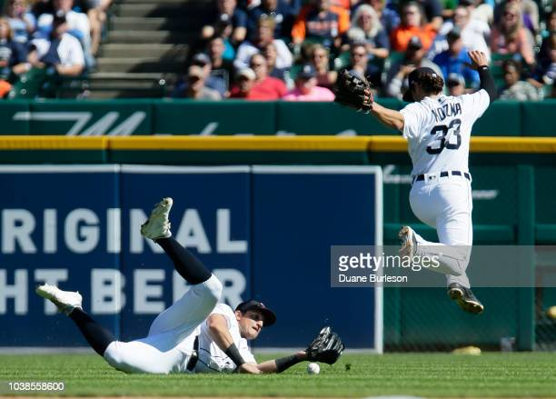 Left fielder Mikie Mahtook of the Detroit Tigers can't come up with a fly ball avoided by shortstop Pete Kozma off the bat of Cam Gallagher of the...