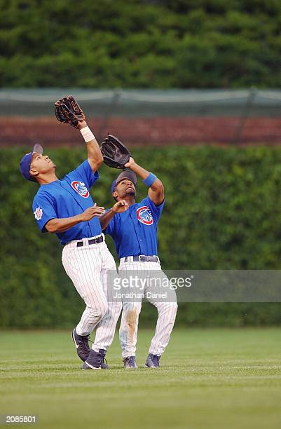 Left fielder Moises Alou and center fielder Cory Patterson of the Chicago Cubs almost collide while trying to catch a pop fly ball during the MLB...