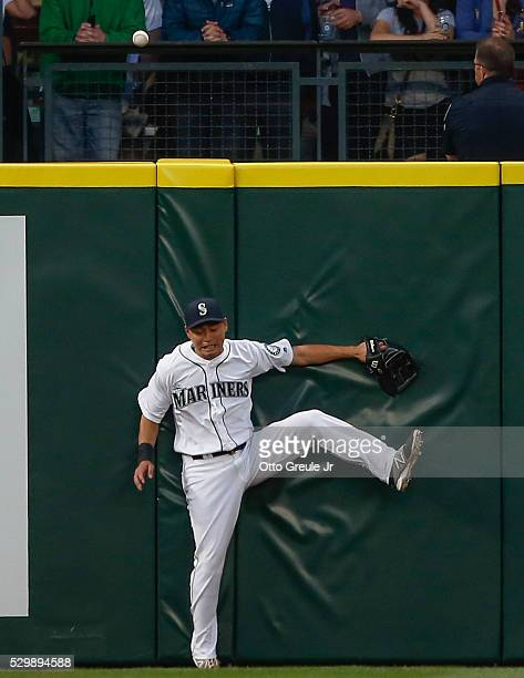 Left fielder Norichika Aoki of the Seattle Mariners leaps at the wall for a home run ball off the bat of Corey Dickerson of the Tampa Bay Rays in the...