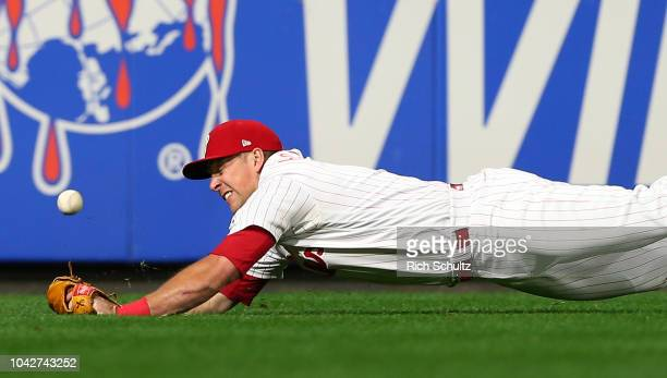 Left fielder Rhys Hoskins of the Philadelphia Phillies dives but can't make a catch on a ball hit by Tyler Flowers of the Atlanta Braves for a double...