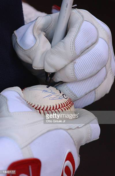 Left fielder Rickey Henderson of the Boston Red Sox autographs a baseball before the MLB game against the Seattle Mariners on August 15 2002 at...
