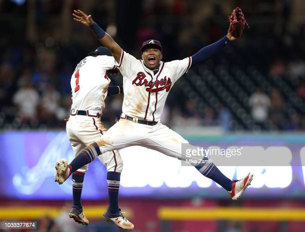 Left fielder Ronald Acuna Jr #13 and second baseman Ozzie Albies of the Atlanta Braves celebrate after the game against the Washington Nationals at...