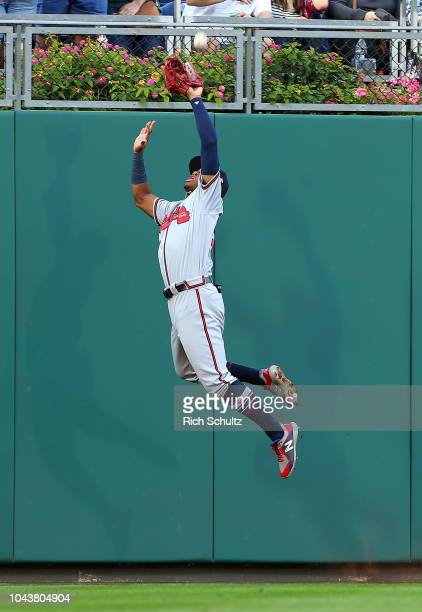 Left fielder Ronald Acuna Jr #13 of the Atlanta Braves makes a leaping catch against the wall on a ball hit by Carlos Santana of the Philadelphia...