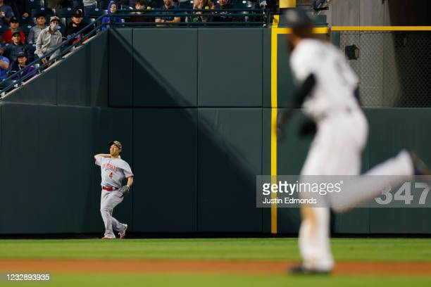 Left fielder Shogo Akiyama of the Cincinnati Reds throws the ball to the infield as Charlie Blackmon of the Colorado Rockies runs to third base on a...