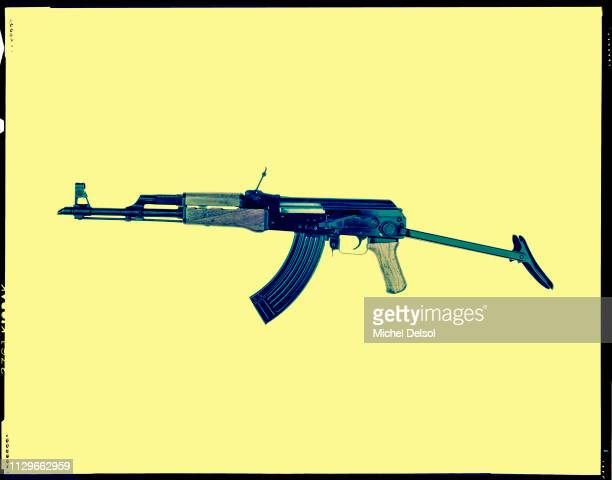 Left profile of an AKM assault rifle with an attached magazine seen against a yellow background New York New York March 9 1994 The photo was taken as...