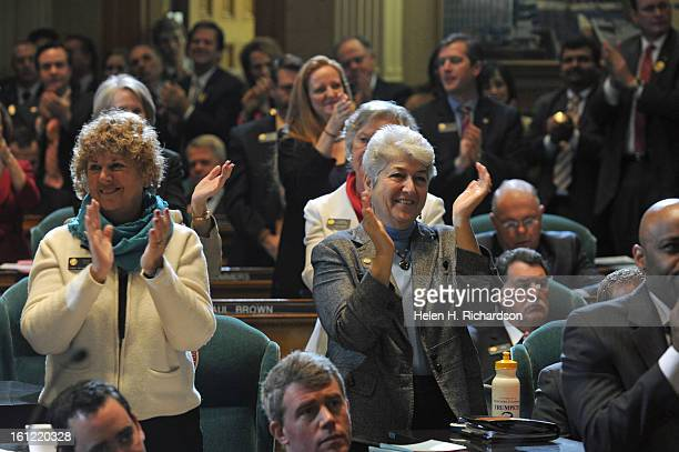 Left Representative Nancy Todd DAurora and right Representative Lois Court DDenver stand an applaud the governor for saying that all civil unions in...