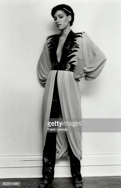 Left; she models low-cut saffron color dress trimmed in black sequins and worn over narrow black sequined pants.