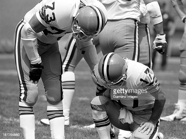 Left tackle Doug Dieken of the Cleveland Browns attends to quaterback Brian Sipe following a play during a game against the Minnesota Vikings on...