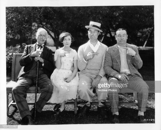 actors Frank Currier Gertrude Olmstead Lawrence Gray and Eddie Gribbon sitting on a bench pointing at each other in a scene from the film 'The...