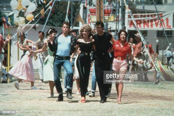Left to right actors Jeff Conaway Olivia NewtonJohn John Travolta and Stockard Channing walk arm in arm at a carnival in a still from the film...