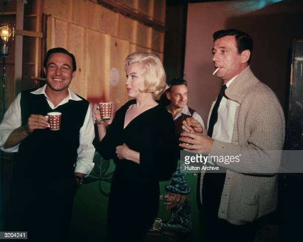 Left to right actors Yves Montand Marilyn Monroe and Gene Kelly laugh while having a coffee break on the set of director George Cukor's film 'Let's...