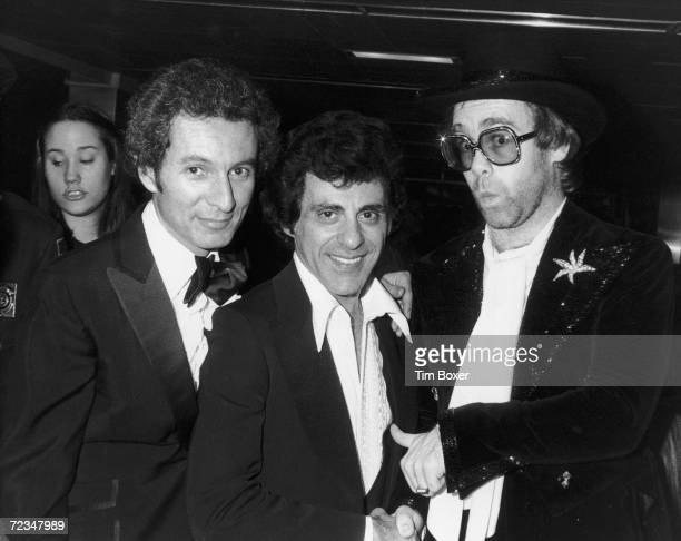 American concert promoter Ron Delsener American singer Frankie Valli and English singer/songwriter Elton John at a party for the premiere of Ken...