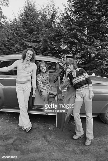 bassist Stanley Sheldon singer and guitarist Peter Frampton and keyboard player Bob Mayo posing with a RollsRoyce USA 3rd June 1977 Mayo is making a...