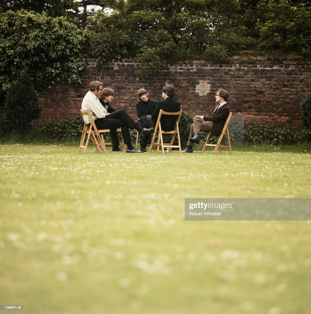 Beatles road manager Mal Evans (1935 - 1976) John Lennon (1940 - 1980), Ringo Starr, Paul McCartney and director Michael Lindsay-Hogg in conference during the making of promotional films for their single 'Rain' and 'Paperback Writer' at Chiswick House grounds, London, 20th May 1966.