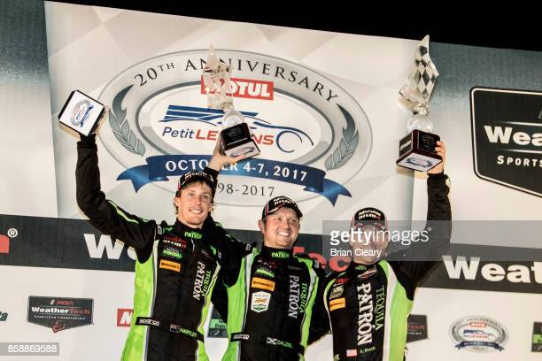 Left to right, Brendan Hartley, of New Zealand, Ryan Dalziel, and Scott Sharp celebrate in victory lane after winning the Motul Petit Le Mans at Road...