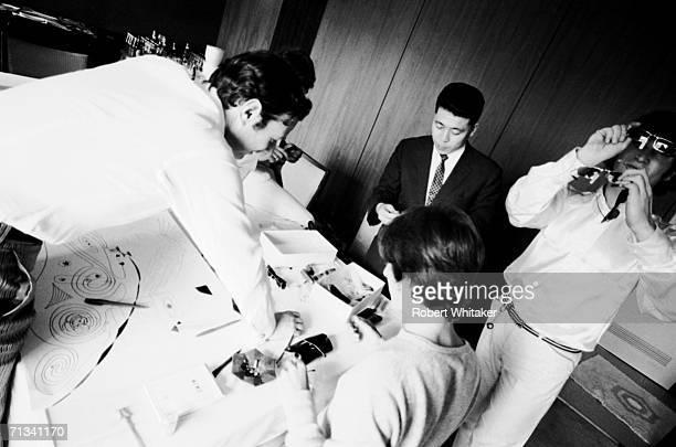 Brian Epstein a Tokyo optician George Harrison and John Lennon inspect some sunglasses inside the Tokyo Hilton Japan 1966
