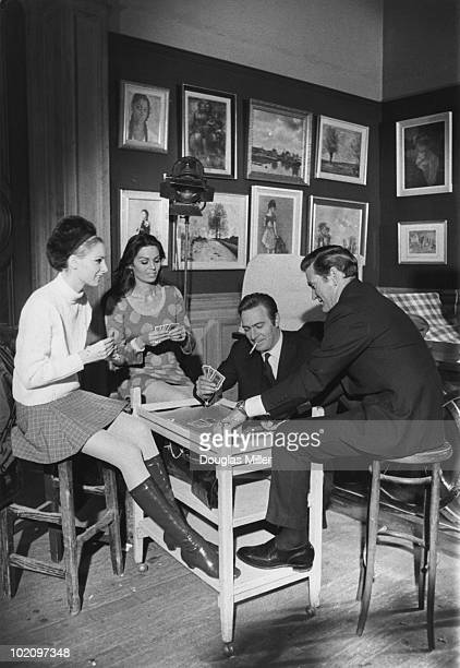Camilla Sparv Daliah Lavi Christopher Plummer and Rod Taylor playing cards during a break in filming 'Nobody Runs Forever' directed by Ralph Thomas...