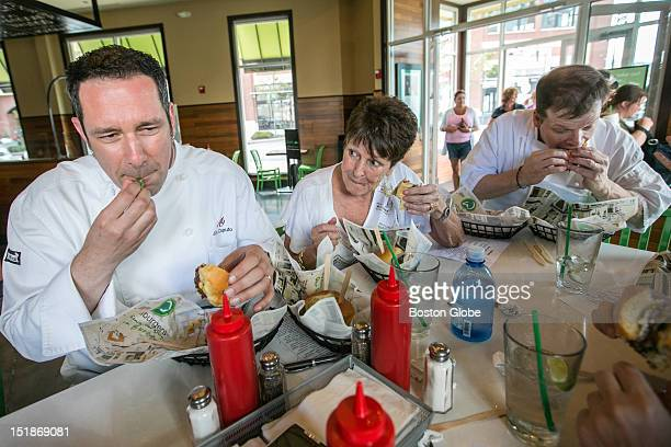 Left to right Chef Jim Caputo Alma Wahlberg and Chef Paul Wahlberg taste test burgers at Wahlburgers in Hingham The restaurant is holding a monthly...