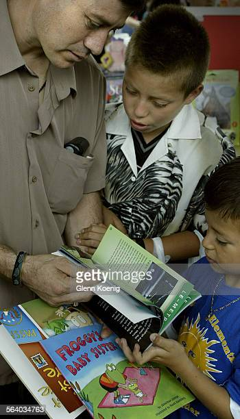 K Left to right Claver DominguezCQ and his sons Osmar Dominguez and Wilfredo Dominguez were exploring the books at the LAUSD Festival of books The...