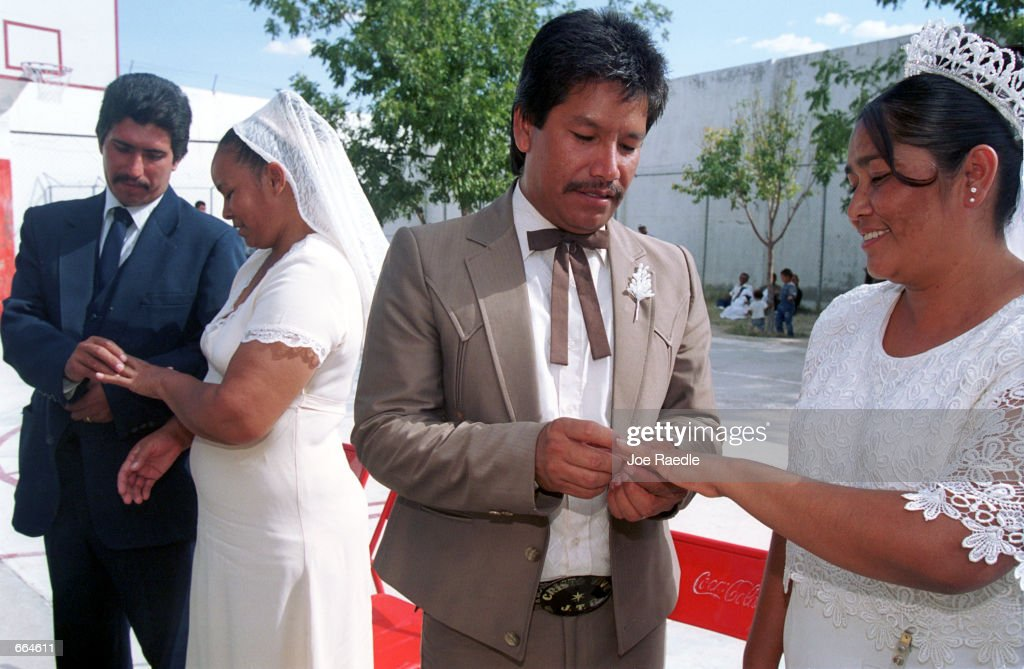 Left to right, Edgar Franco, Graciela Chacon, Juan Tejada Rodriguez, and Marignacia Rodriquez Hernandez exchange rings during a wedding ceremony at a prison October 2, 2000 in Ciudad Juarez, Mexico. Mexican law allows for inmates to marry inside prison walls. 5 couples, one current inmate and four former inmates were married by their church pastor. (Photo by Joe Raedle/Newsmakers) TO