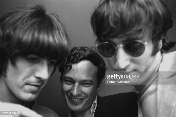George Harrison Brian Epstein and John Lennon examine a Polaroid photograph at the Westwood Hotel in Anchorage Alaska 27th28th June 1966 En route for...
